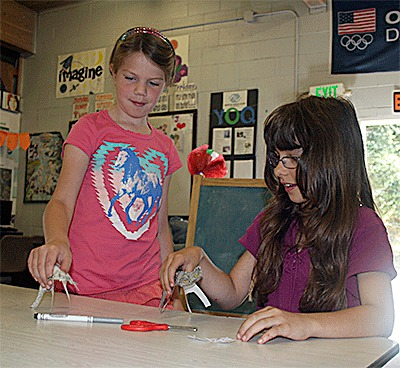 Emma Brewer, left, and Jessica Piccone take part in a crafts project at the Boys and Girls Club this summer.— Image Credit: Jim Waller / Whidbey Examiner